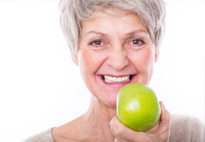 Smiling senior woman with an apple