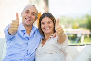 Couple smiling giving the thumbs up