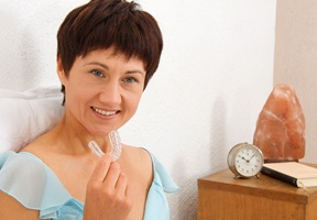 A woman in bed holding an oral appliance