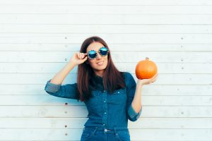 Woman smiling and holding pumpkin