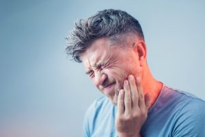 man with dental emergency holding mouth in pain