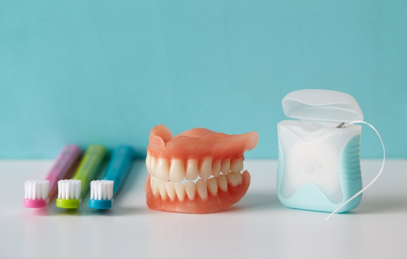 Dentures next to toothbrushes and floss