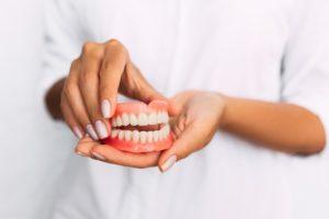Hands holding new set of dentures.