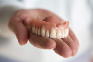 Hand holding model for soaking dentures