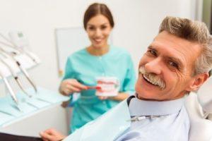 Older man at dental checkup with dentures